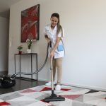 Crown Maids - Cleaning lady is vacuuming the carpet